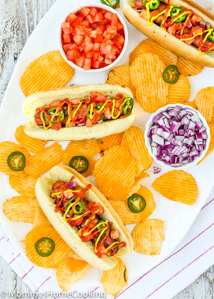 These Easy Bacon-Wrapped Hot Dogs are perfect for a summer weeknight dinner!! Topped with tomato, onion, and jalapeno, this hot dog is a deliciously easy way to say bye-bye to the Ol' boring bun. http://mommyshomecooking.com