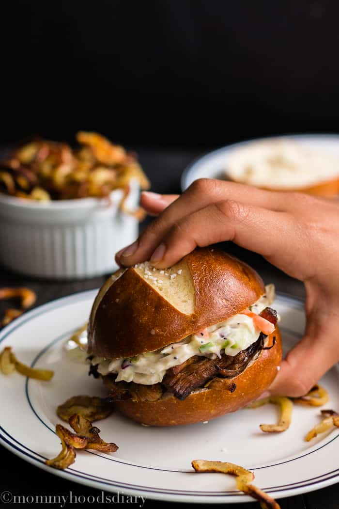 a hand grabbing a Cranberry Pulled Pork and Coleslaw Salad Sandwich