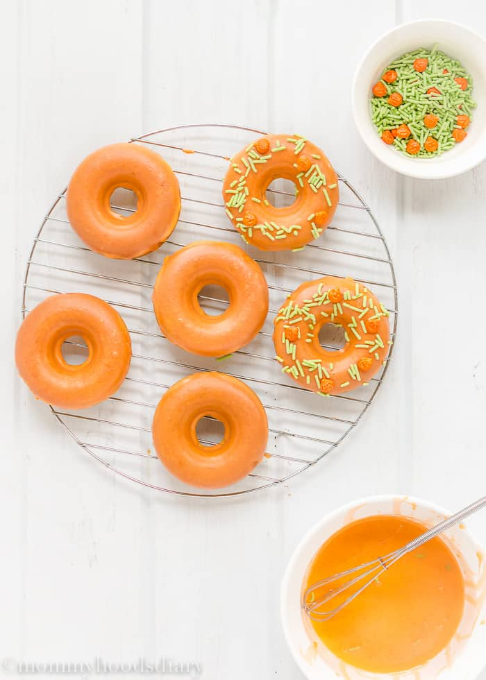 These Easy Baked Pumpkin Doughnuts are delicious and moist donuts! Loaded with tons of fall flavors and sprinkled with Halloween fun. https://mommyshomecooking.com