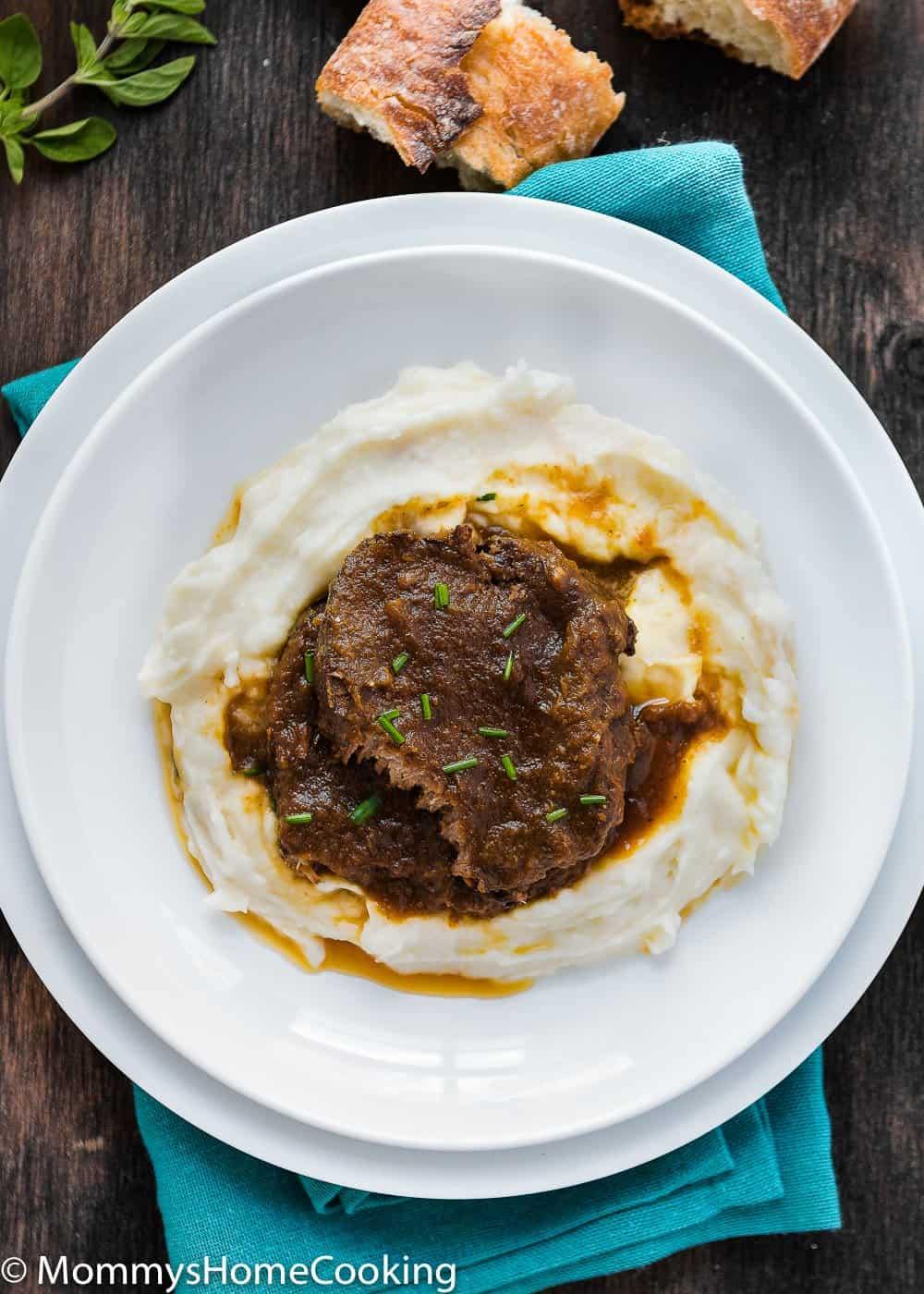 Venezuelan Asado Negro in a white plate with mashed potatoes and sauce