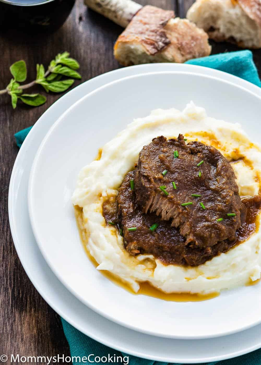 Venezuelan Asado Negro in a white plate with mashed potatoes  and garnished with chives