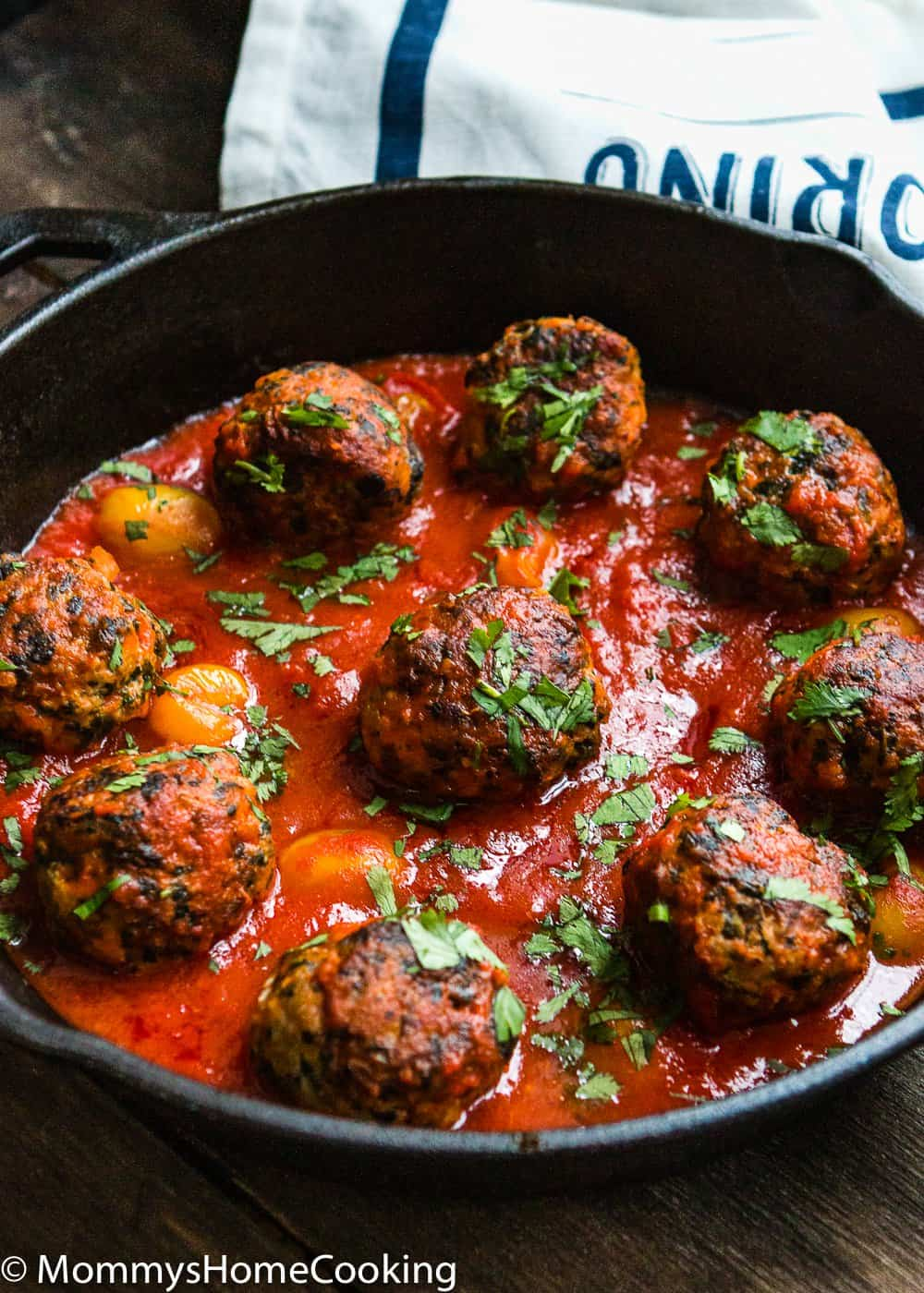 Eggless turkey meat balls with tomato sauce in a cast iron skillet.