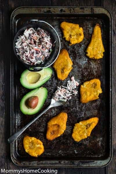 fried tostones in a baking sheet with coleslaw and avocado