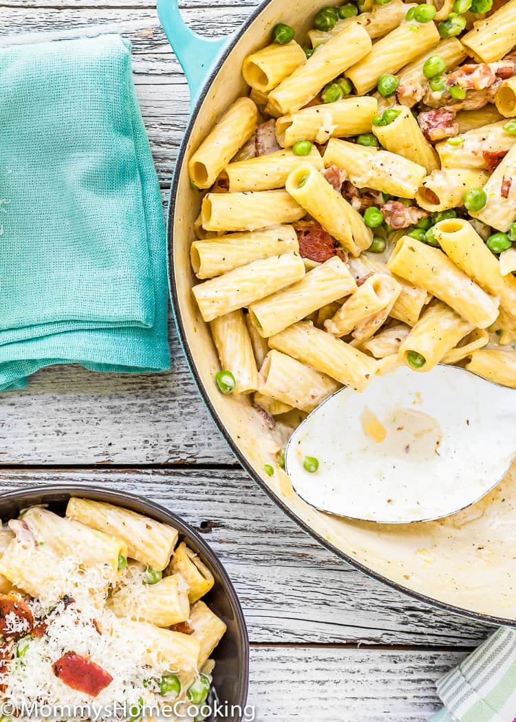 Creamy Alfredo Pasta with Bacon and Peas in a pot with a serving spoon