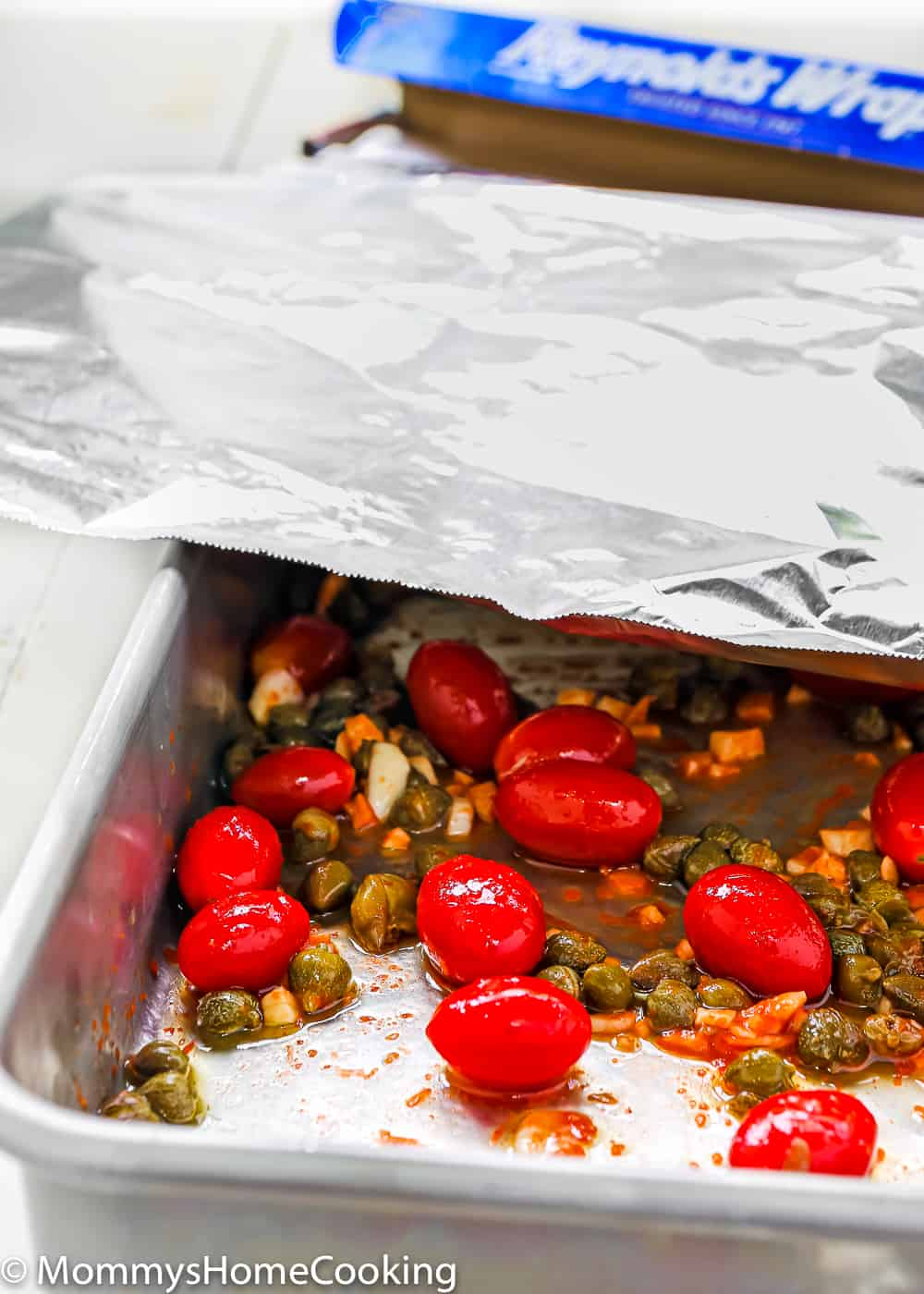 Easy roasted tomatoes and cappers in a baking pan cover with foil