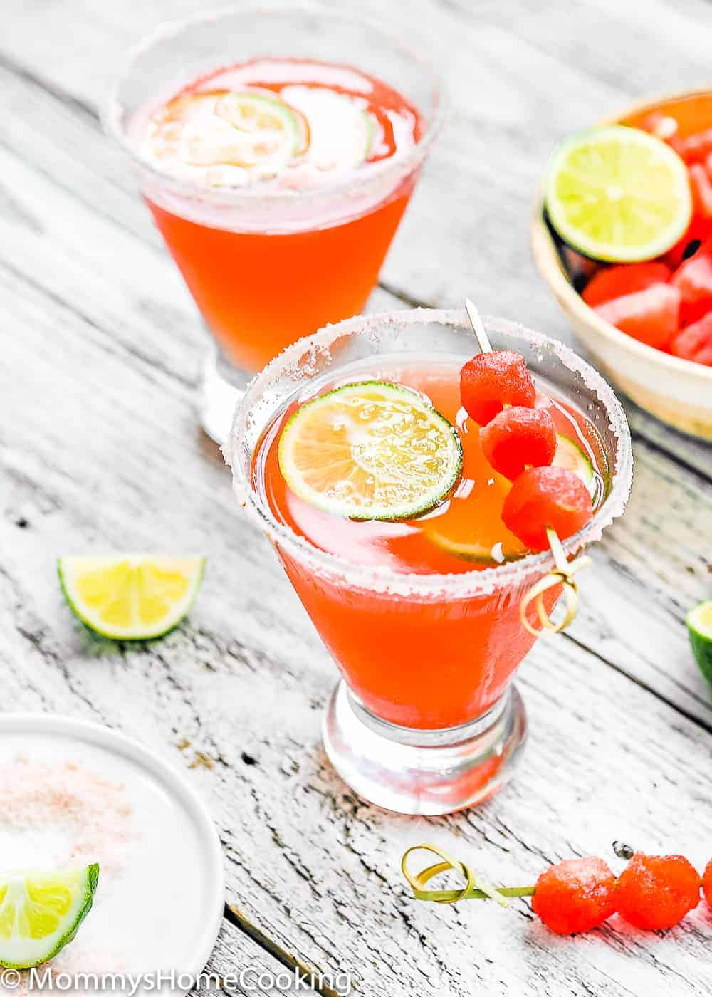 2 glasses with watermelon cocktail , sliced limes and watermelon balls