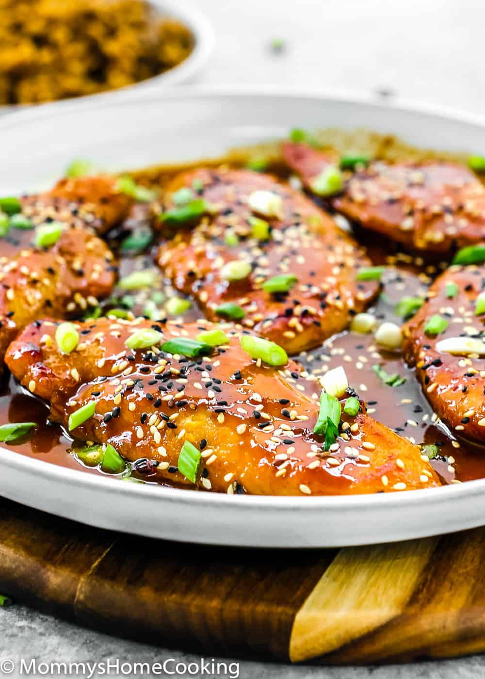 Easy Asian-Style Chicken Breasts in a white skillet  with tasty sauce