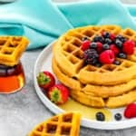eggless waffles stack with fresh fruit on a gray surface