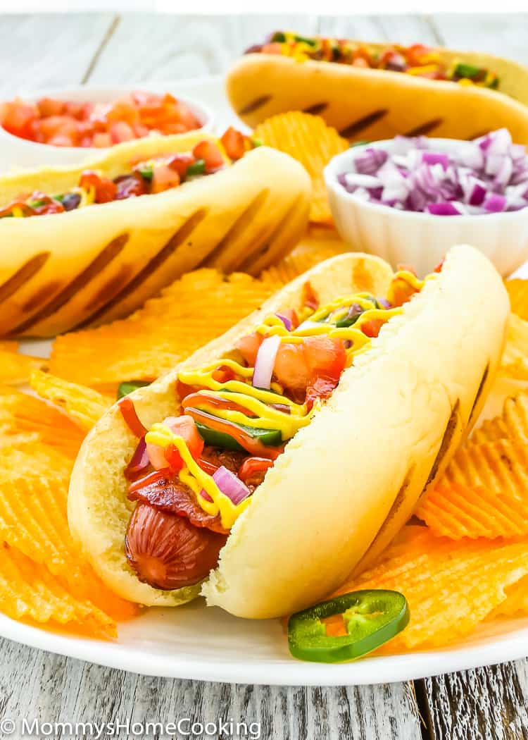 These Easy Bacon-Wrapped Hot Dogs are perfect for a summer weeknight dinner!! Topped with tomato, onion, and jalapeno, this hot dog is a deliciously easy way to say bye-bye to the Ol' boring bun.