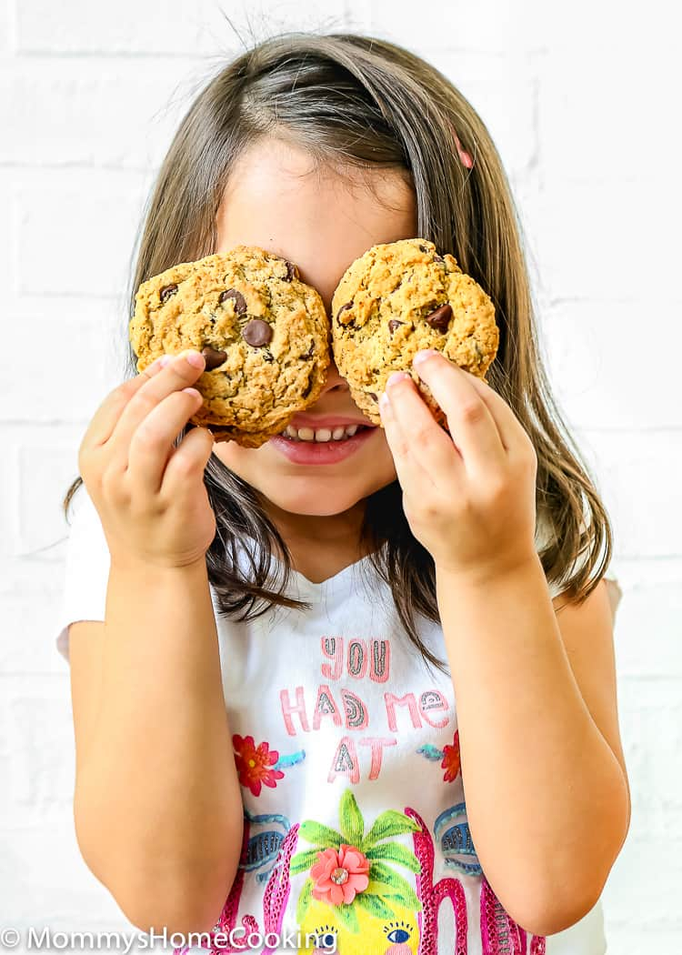girl holding two eggless chocolate chip cookies