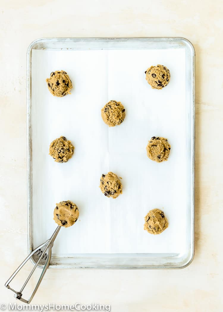 raw eggless chocolate chip cookies balls dough in a baking sheet