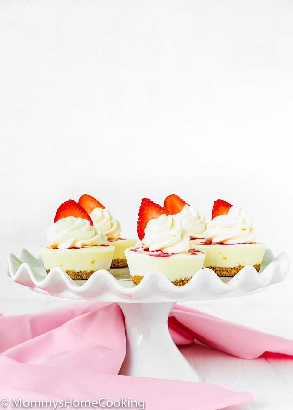 Mini Greek Yogurt Strawberry Cheesecakes in a serving plate topped with fresh strawberries