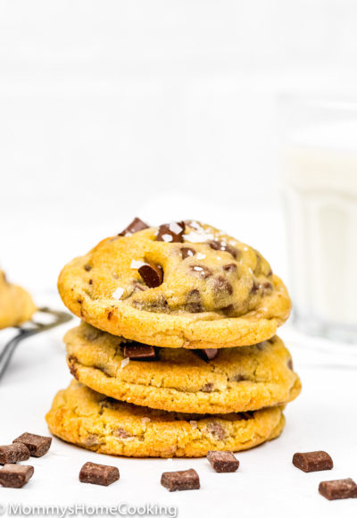 Eggless Chocolate Chip Cookies with sea salt stack with a glass of milk in the background