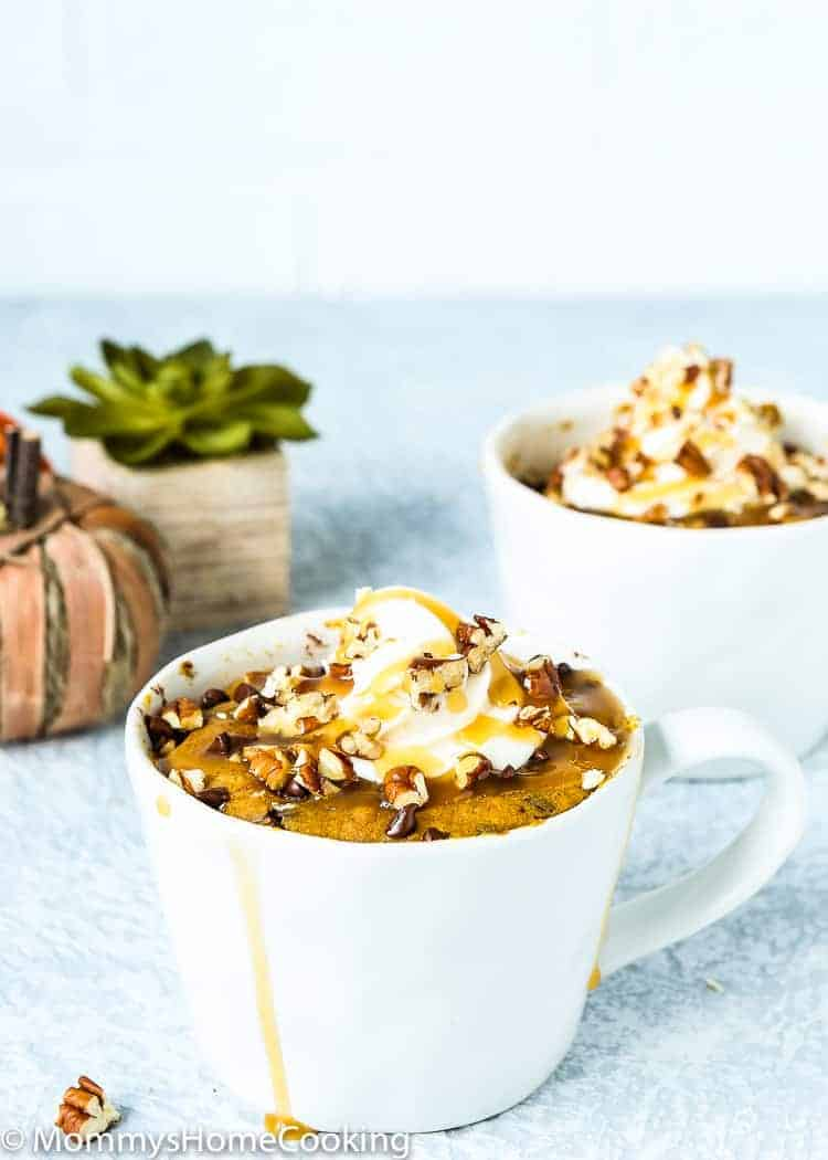 Eggless Chocolate Chip Pumpkin Bread in a Mug with whipped frosting and chopped nuts
