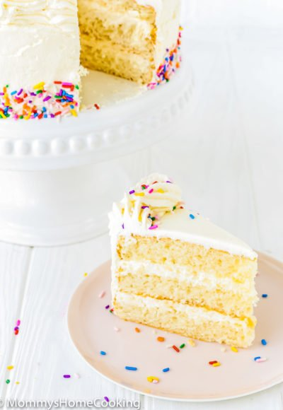 eggless vanilla cake on a cake stand next to plate with a slice of cake