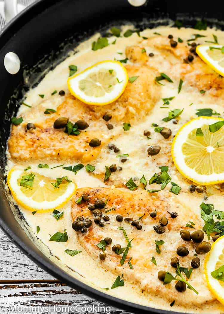 creamy chicken piccata in a skillet with lemon slices