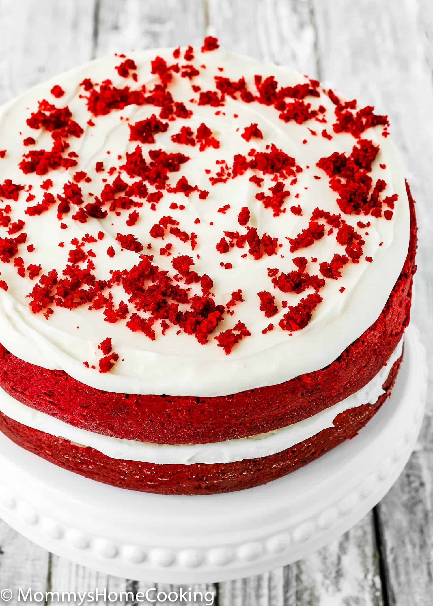 This Eggless Red Velvet Cake is moist, rich, and amazingly tasty! Two lovely layers of tender vibrant sponge red cake with fluffy cream cheese frosting. I promise you will not miss the eggs.  This easy dessert is the perfect showstopper for any occasion. https://mommyshomecooking.com