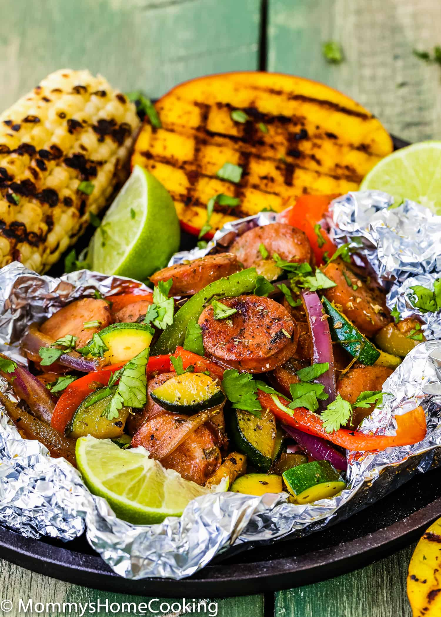 These Easy Sausage and Veggies Foil Packets with Grilled Chipotle Mangoes are perfect for grilling in the backyard or cooking on camping trips! No fuss. No cleaning involved. Plus, they're fun to make. Grill and oven instructions included.  https://mommyshomecooking.com