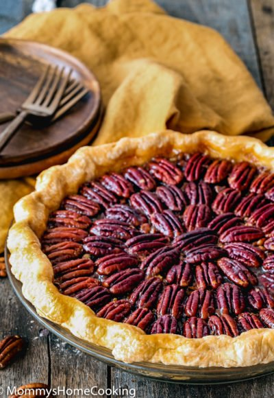 egg-free pecan pie in a pie dish on a wooden surface with plates, forks and napkin on the background