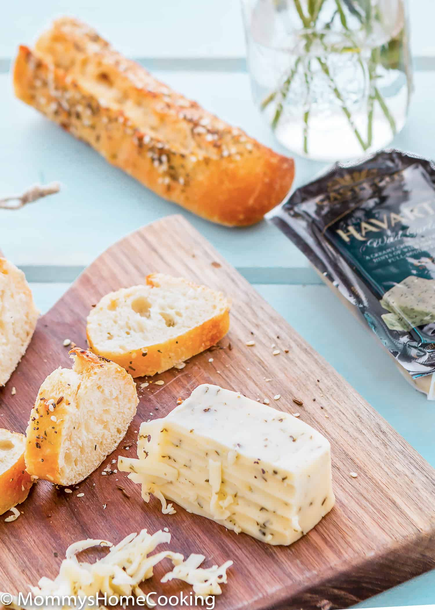 wooden cheeseboard with havarti cheese and bread