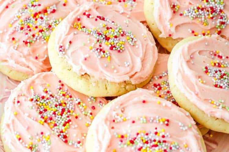 A plate with eggless sugar cookies frosted with pink buttercream and sprinkle.
