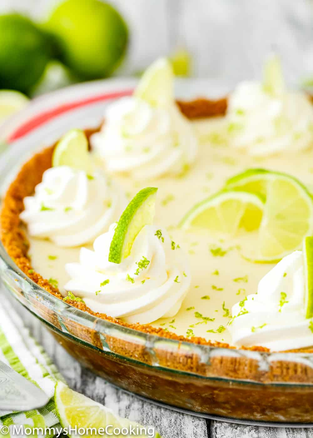 eggless key lime pie decorated with whipped cream and small lime wedges