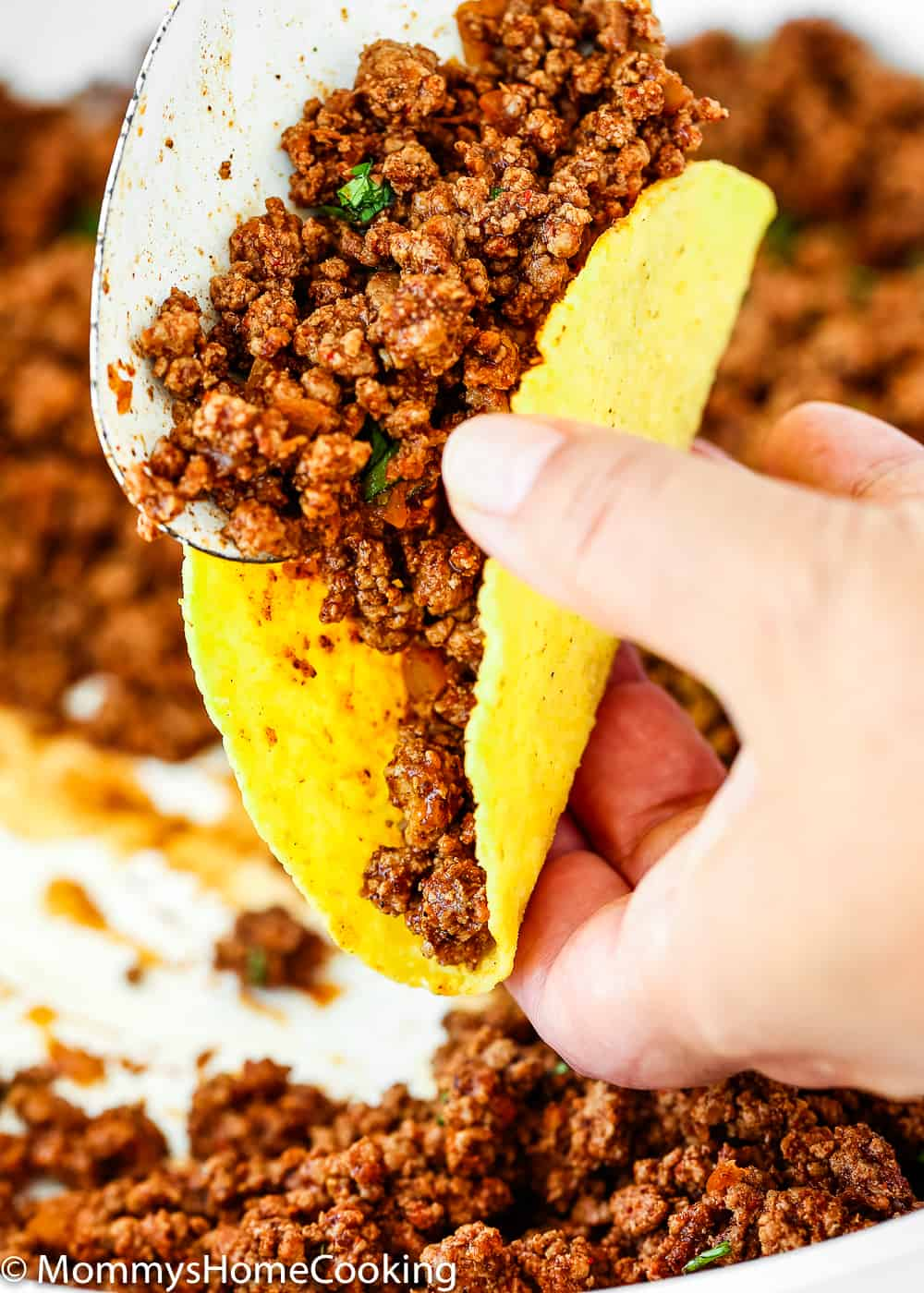 Serving taco ground beef into a taco shell