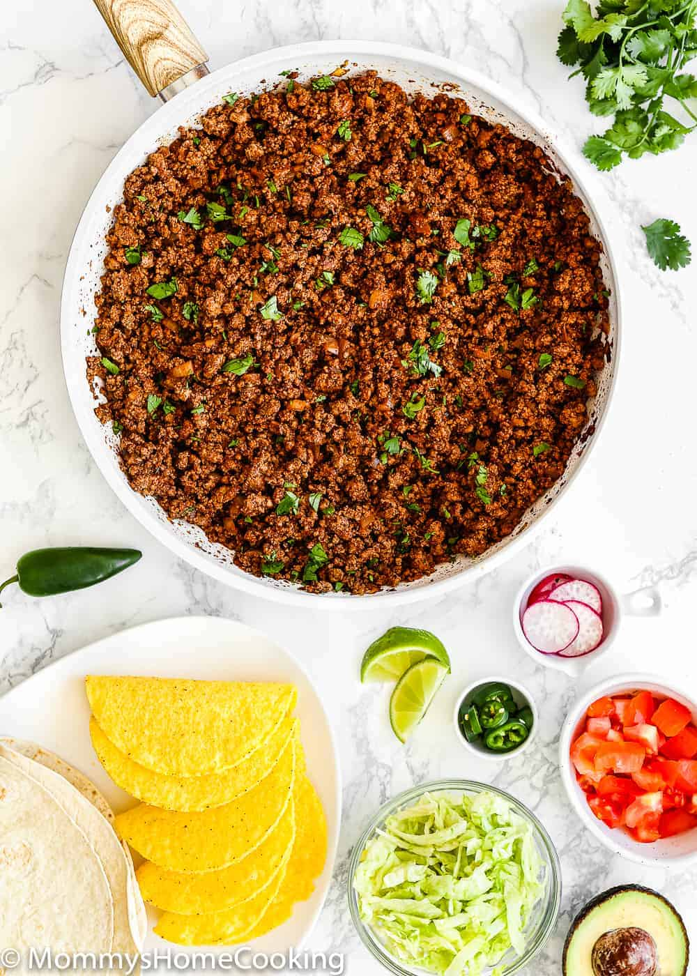 Cooked Ground Beef for Tacos in a skillet surrounded by taco toppings
