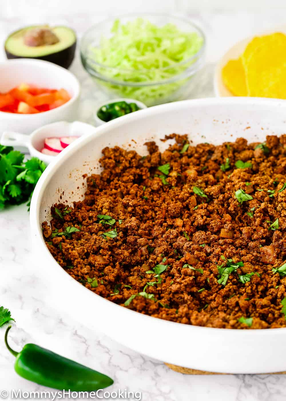 Cooked Ground Beef for Tacos in a white skillet  surrounded by taco toppings