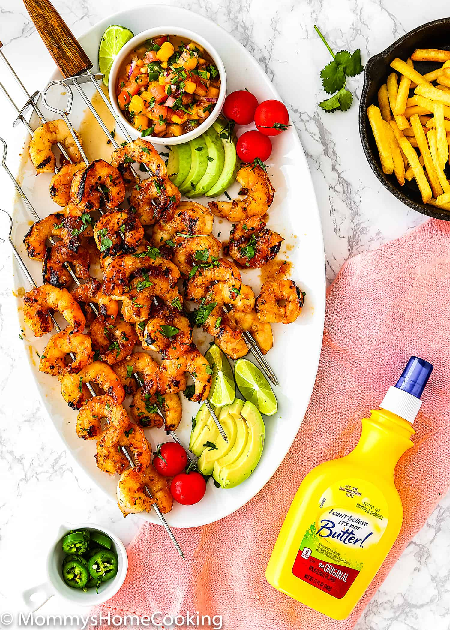 Honey Chipotle Grilled Shrimp in a white oval plate served with sliced avocado, cherry tomatoes, mango salsa and bottle of I Can't Believe It's Not Butter! Original Spray