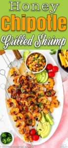 Honey Chipotle Grilled Shrimp in a white oval plate served with sliced avocado, cherry tomatoes and mango salsa