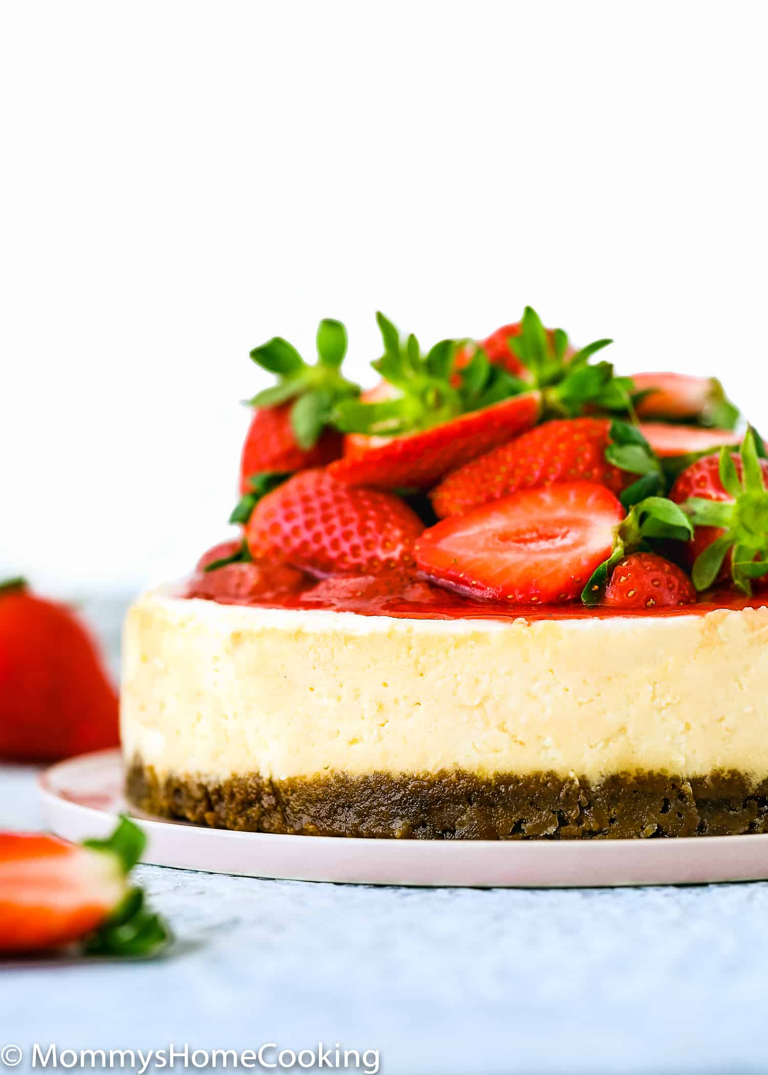 Eggless Cheesecake topped with strawberry sauce/topping and fresh strawberries