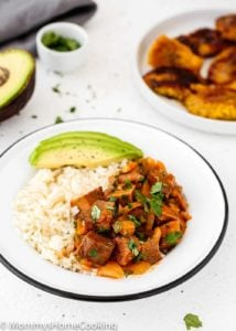 cooked Beef tongue in tomato sauce in a plate with sweet plantains, white rice and avocado