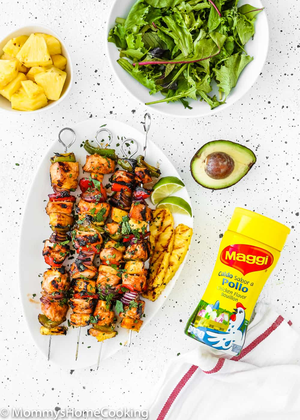Easy Grilled Hawaiian Chicken Skewers in a white plate with chopped fresh pineapple, green salad, avocado and a granulated chicken Bouillon bottle