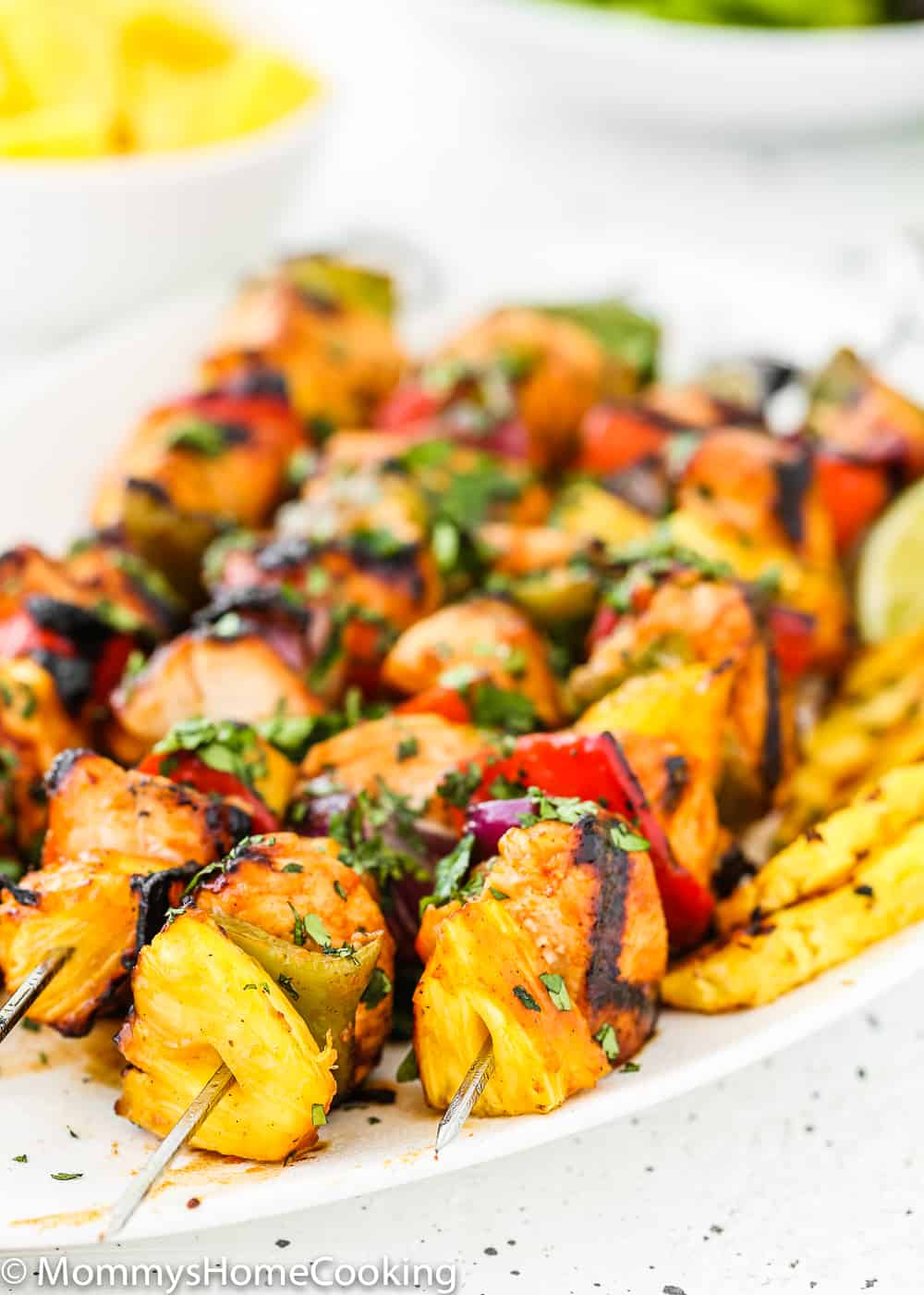 Easy Grilled Hawaiian Chicken Skewers in a white plate with lemon wedges and grilled pineapple close up