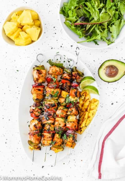 Easy Grilled Hawaiian Chicken Skewers in a white plate with chopped fresh pineapple, green salad and avocado