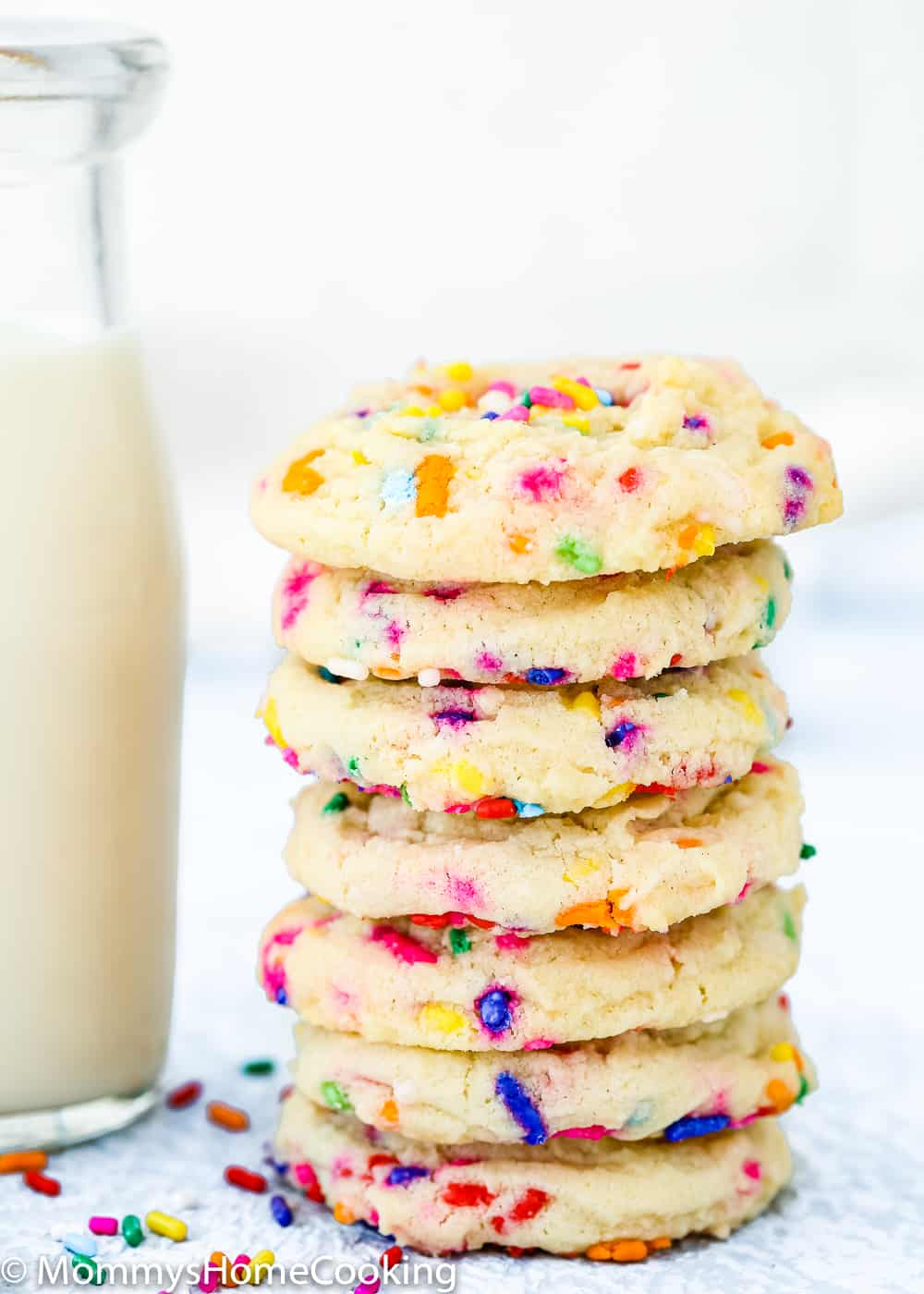 stack of Eggless Funfetti Cookies with a glasses of milk
