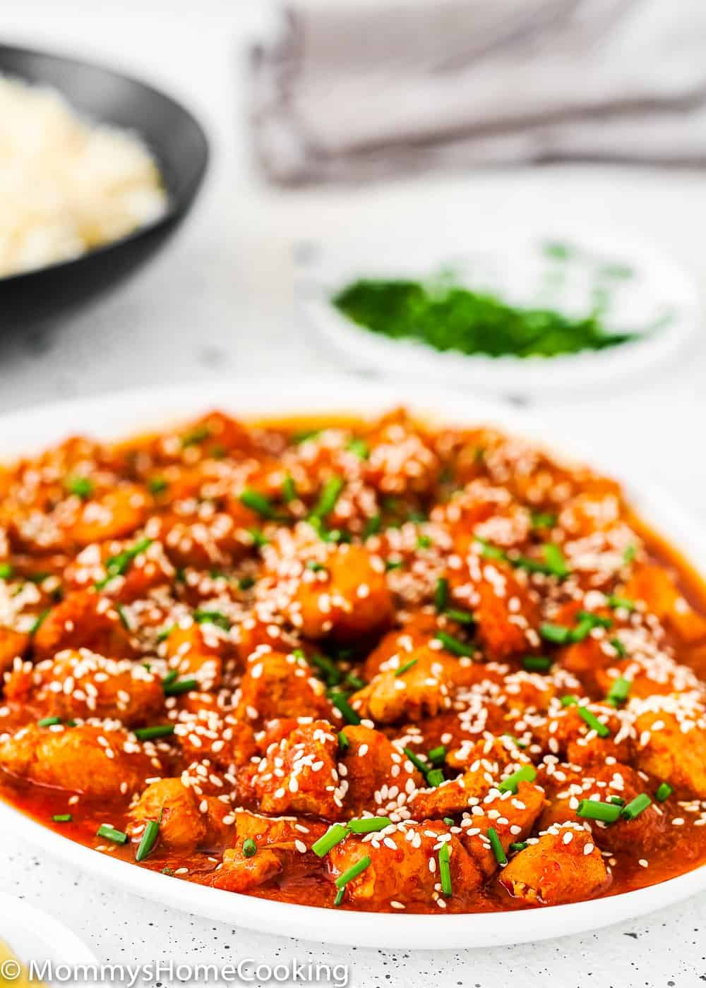 Instant Pot Korean Kimchi Chicken in a white plate sprinkle with sesame seed and chives