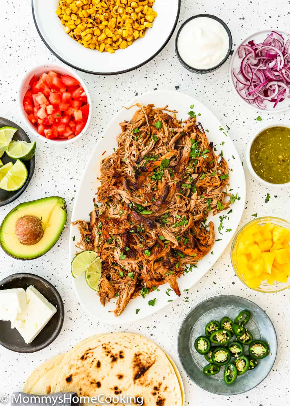 Slow Cooker Chipotle Carnitas on a serving platter with all the ingredients for a taco bar.