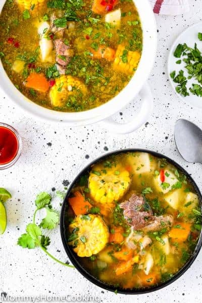 Venezuelan Sancocho in a bowl over a table with hot sauce and lime wedges