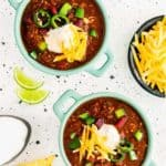 two bowls of easy instant pot chili topped with sliced jalapeño, sour cream and cheese