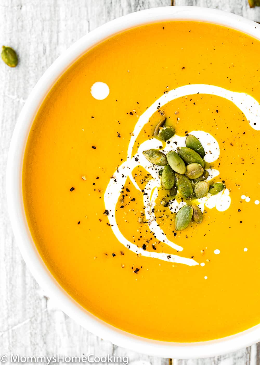 Instant Pot Pumpkin Soup in a bowl with cream and pumpkin seeds
