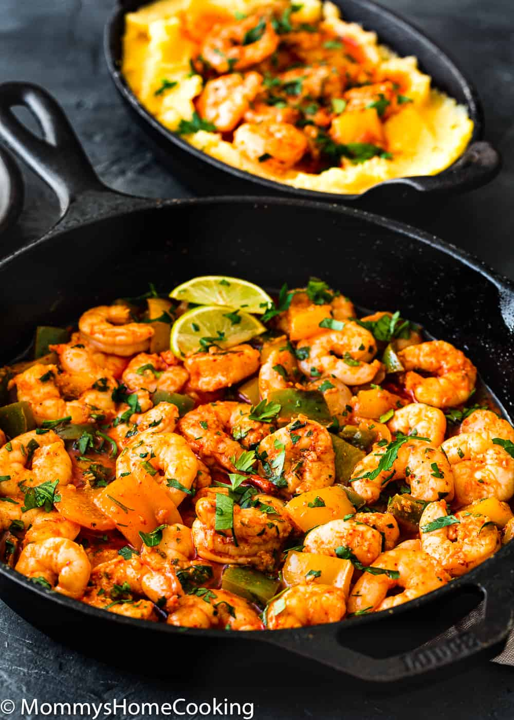 Easy Peri Peri Shrimp in a cast iron skillet garnished with parsley and lemon wedges