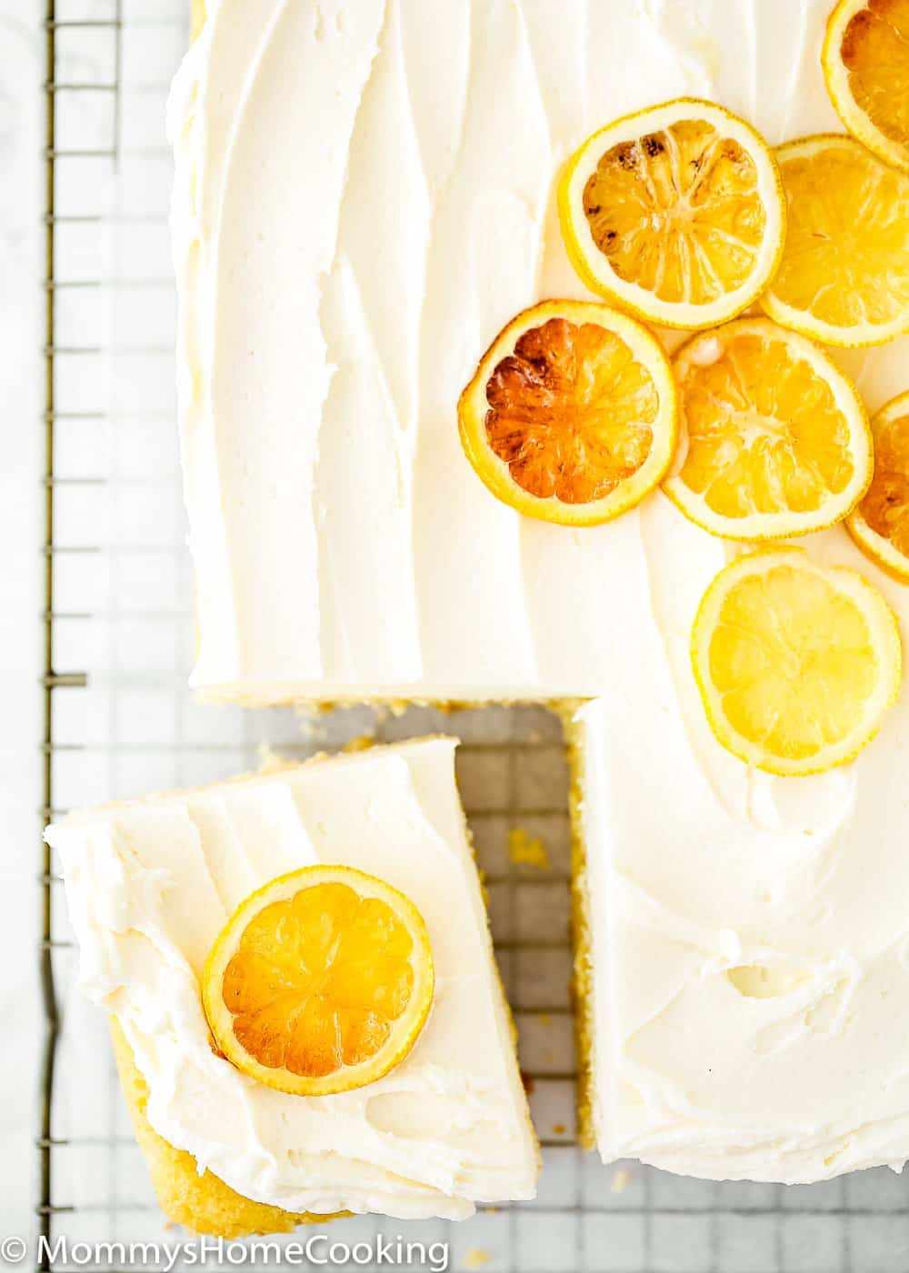 Eggless Lemon Cake over a cooling rack with candied lemon slices