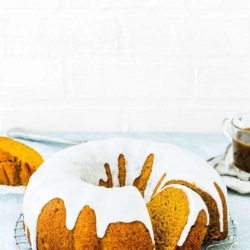 Eggless Pumpkin Cake over a cooling rack with sugar glaze