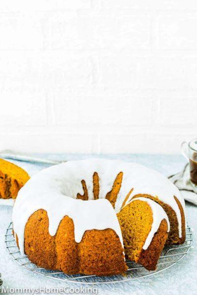Eggless Pumpkin Cake over a cooling rack with sugar glaze