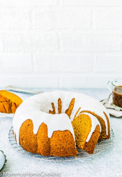 sliced Eggless Pumpkin Cake with glaze over a cooling rack with a cup of coffee in the background