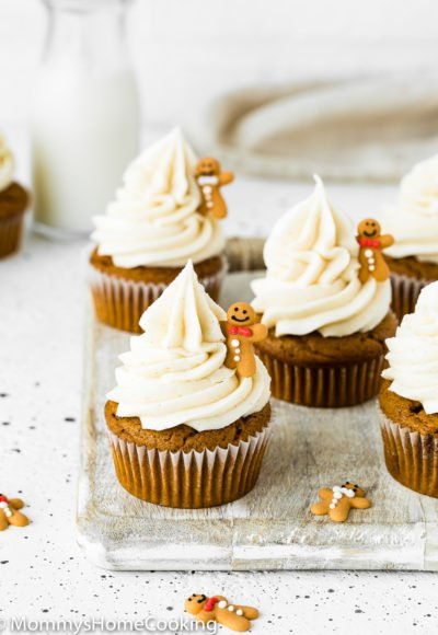 Eggless Gingerbread Cupcakes with cinnamon cream cheese frosting over a wooden surface with a bottle of milk in the background