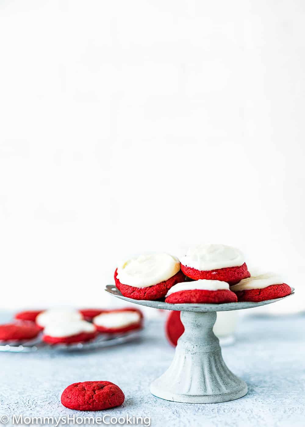 eggless red velvet cookies with cream cheese frosting in a cake stand
