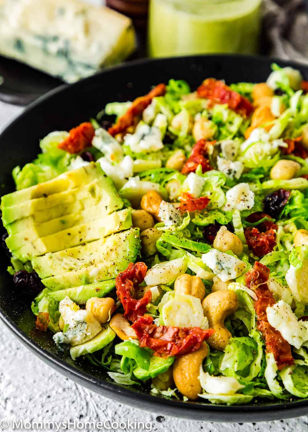 Easy Shaved Brussel Sprout Salad with Cranberries and avocado in a black bowl